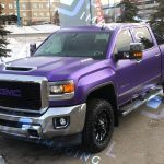 A pearlescent-purple color-change vinyl vehicle wrap installed on a GMC 3500 HD pickup truck.