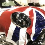 Unfinished installation of a custom-printed vinyl vehicle wrap of the United Kingdom Union Jack flag on a Cooper Mini car.